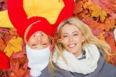 放置在叶子和微笑的两个愉快的女朋友 免版税图库摄影