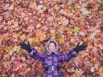 放置在叶子的妇女愉快 库存照片