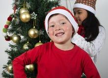 放置在圣诞树下的愉快的孩子 免版税库存照片