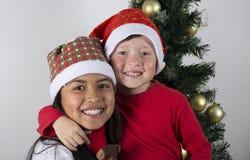 放置在圣诞树下的愉快的孩子 库存照片