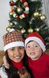 放置在圣诞树下的愉快的孩子 免版税图库摄影