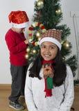 放置在圣诞树下的愉快的孩子 图库摄影