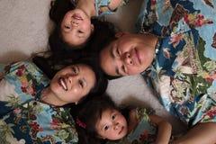 放置在地板微笑的亚洲家庭 免版税库存图片