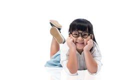 放置在地板的小亚裔逗人喜爱的女孩隔绝与裁减路线 免版税库存照片