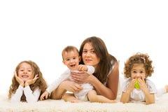 放置在地毯的妈妈和三个孩子 免版税库存图片