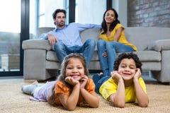 放置在地毯的孩子在客厅 免版税库存图片