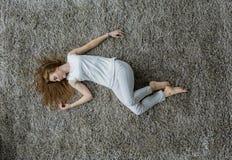 放置在地毯的少妇 库存照片