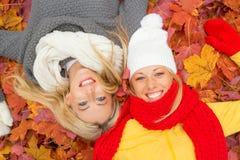 放置在地面上的两个愉快的女朋友 免版税库存图片