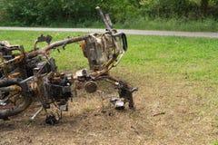 放置在地面金属垃圾背景的被烧的摩托车 免版税库存图片