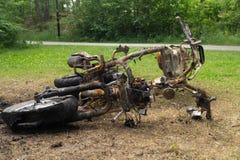 放置在地面金属垃圾背景的被烧的摩托车 库存照片