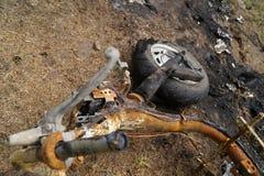 放置在地面金属垃圾背景的被烧的摩托车 免版税图库摄影