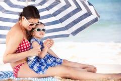 放置在太阳奶油的母亲和女儿 免版税库存图片