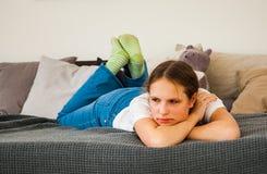 放置在她的床上的牛仔裤的十几岁的女孩 免版税库存照片
