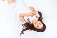 放置在她的床的年轻愉快的亚裔妇女使用她的智能手机t 免版税库存图片