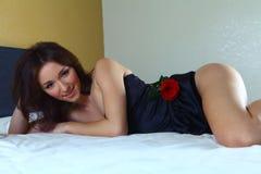放置在床的性感的妇女穿着黑女用贴身内衣裤 免版税库存照片
