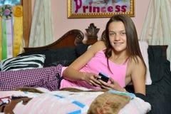 放置在她的床的逗人喜爱的女孩-发短信 免版税库存照片