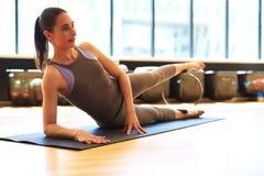 放置在她的旁边做的腿部锻炼的少妇 免版税库存图片