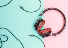 放置在平的桃红色和蓝色表面的花梢耳机 模式导线构筑布局 库存图片