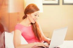 放置在床上的妇女放松使用工作在她的便携式计算机 库存照片