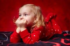 放置在床上的沉思小孩女孩用手在下巴 图库摄影