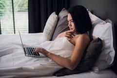 放置在床和使用膝上型计算机的年轻美丽的白种人妇女工作,在醒和考虑工作后 复制空间 免版税图库摄影