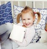 放置在床愉快微笑,生活方式人概念的小逗人喜爱的女孩 免版税库存照片