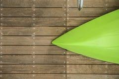 放置在有一部分的一个自然木船坞的被弄翻的绿色皮船弓的镀铬物扶手栏杆在边 图库摄影