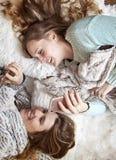 放置在有电话笑的毯子的愉快的朋友 免版税库存照片