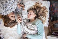 放置在有电话笑的毯子的愉快的朋友 免版税图库摄影