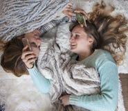 放置在有电话笑的毯子的愉快的朋友 免版税库存图片