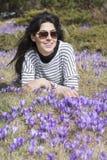 放置在有紫色开花的番红花的一个草甸的旅游妇女 免版税库存图片