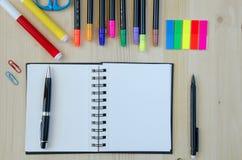 放置在木书桌背景的办公用品 顶视图 铅笔,剪刀,标志,贴纸,书签,玻璃 免版税库存照片