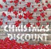 放置在木背景的圣诞节折扣和红色落的叶子 图库摄影