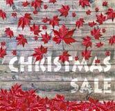 放置在木背景的圣诞节销售和红色落的叶子 免版税库存图片