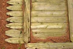 放置在杉木针的粗砺的木篱芭 库存照片