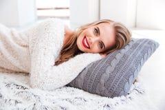 放置在枕头的一名微笑的愉快的妇女的画象 免版税库存图片