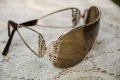 放置在桌的布朗太阳镜 金属的蝴蝶 库存照片