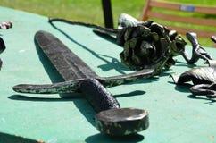 放置在桌的手工制造剑室外 图库摄影
