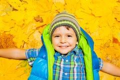 放置在桔子和黄色叶子的愉快的男孩 库存照片