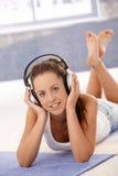 放置在楼层的有吸引力的女性听的音乐 库存照片