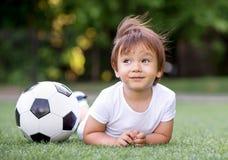放置在橄榄球场的腹部的小小孩孩子在足球和作梦附近 风挥动孩子的头发 未来运动员 免版税库存照片