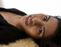 放置在毛皮地毯的一名轻松的性感的妇女 免版税图库摄影