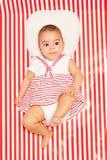 放置在毯子的镶边礼服的非洲婴孩 库存图片
