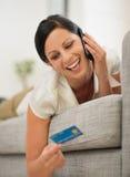 放置在沙发告诉的移动电话的愉快的妇女 库存图片