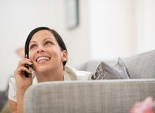 放置在沙发和告诉的移动电话的愉快的妇女 库存照片