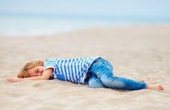 放置在沙滩的疲乏,但是愉快的年轻男孩在用尽休闲比赛以后 图库摄影