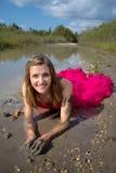 放置在泥的正式舞会礼服的女孩 免版税库存照片