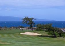 放置在海洋旁边的高尔夫球运动员在卡帕拉奥阿 免版税库存照片