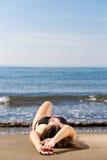 放置在海海滩的年轻美丽的被晒黑的妇女 免版税图库摄影