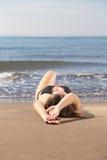 放置在海海滩的年轻美丽的被晒黑的妇女 免版税库存照片